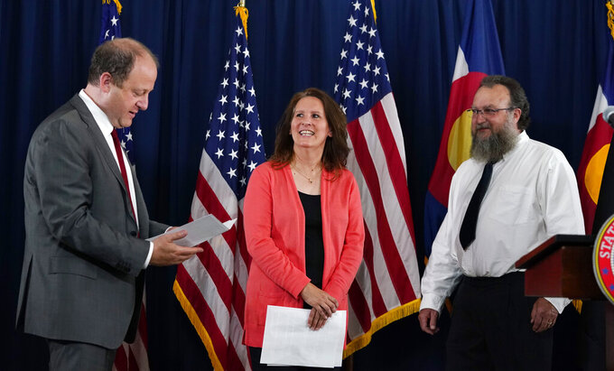 Sally Sliger, center, Colorado's first $1-million winner for receiving the COVID-19 vaccine, and her husband, Chris, right, joke with Colorado Governor Jared Polis during a news conference to announce the awarding of the prize Friday, June 4, 2021, at the governor's mansion in Denver. Colorado will award four more $1-million prizes in the next month to residents who have been vaccinated. (AP Photo/David Zalubowski)