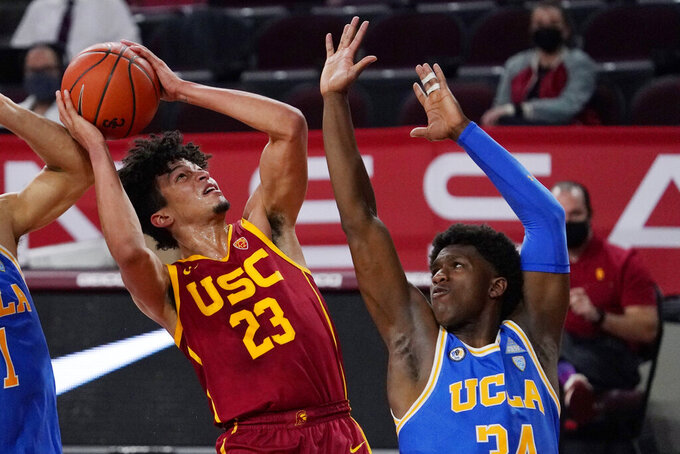Southern California forward Max Agbonkpolo, left, shoots as UCLA guard David Singleton defends during the second half of an NCAA college basketball game Saturday, Feb. 6, 2021, in Los Angeles. USC won 66-48. (AP Photo/Mark J. Terrill)
