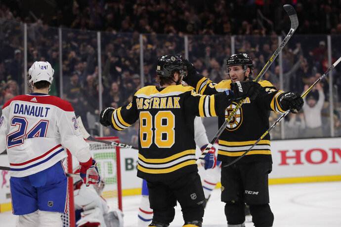Boston Bruins right wing David Pastrnak (88) is congratulated by Patrice Bergeron after his third goal of the game during the second period of an NHL hockey game in Boston, Wednesday, Feb. 12, 2020. At left is Montreal Canadiens center Phillip Danault (24). (AP Photo/Charles Krupa)