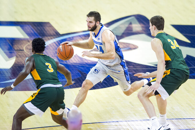 Creighton's Mitch Ballock, center, runs the offense against North Dakota State's Tyree Eady, left, and Rocky Kreuser during the second half of an NCAA college basketball game in Omaha, Neb., Sunday, Nov. 29, 2020. (AP Photo/Kayla Wolf)