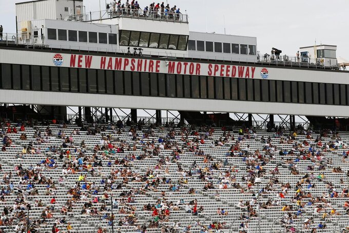 Fans sit socially distanced, due to the coronavirus pandemic, in the grandstand during a NASCAR Cup Series auto race, Sunday, Aug. 2, 2020, at the New Hampshire Motor Speedway in Loudon, N.H. (AP Photo/Charles Krupa)