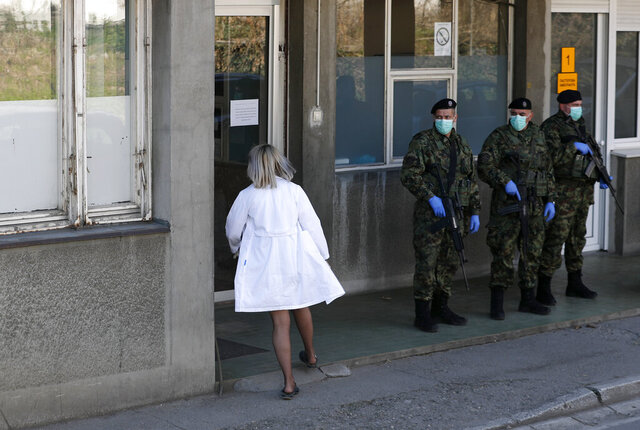 In this photo taken Monday, March 16, 2020, Serbian Army soldiers stand guard outside the Clinic for Infectious and Tropical Diseases in Belgrade, Serbia. Although the global COVID-19 pandemic has not hit Eastern and Central Europe with such a force compared to Italy, Spain and France, health officials throughout the region are sounding alarm about the lack of medical staff, facilities, equipment and enough hospital beds to handle several virus outbreaks simultaneously. For most people, the new coronavirus causes only mild or moderate symptoms. For some it can cause more severe illness. (AP Photo/Darko Vojinovic)