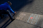 Kimberly Miller, of the Brooklyn borough of New York, who is with Gays Against Guns, leaves a chalk message honoring Justice Ruth Bader Ginsburg on a Washington Square Park walkway in New York Saturday, Sept. 19, 2020, a day after the death of the Supreme Court justice. (AP Photo/Craig Ruttle)