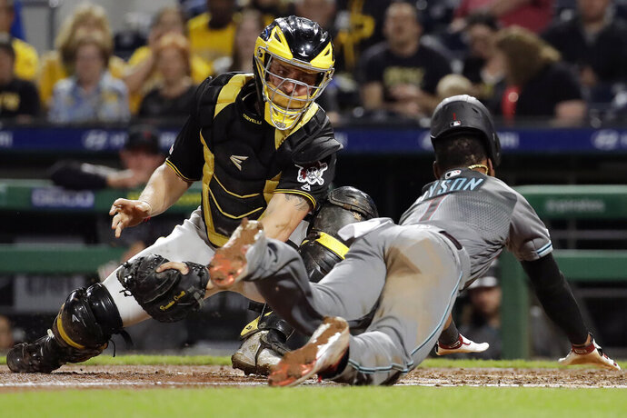 Pittsburgh Pirates catcher Francisco Cervelli, left, can't get the tag on Arizona Diamondbacks' Jarrod Dyson who scores from third on a fielder's choice by David Peralta in the sixth inning of a baseball game in Pittsburgh, Tuesday, April 23, 2019. (AP Photo/Gene J. Puskar)