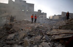 Palestinian firefighters check the dame of destroyed buildings hit by Israeli airstrikes early morning in Gaza City, Saturday, Oct. 27, 2018. Israeli aircraft have struck dozens of militant sites across the Gaza Strip as militants fired some 30 rockets into Israel. (AP Photo/Khalil Hamra)