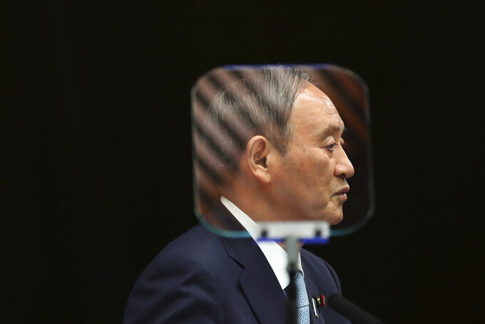 FILE - In this Sept. 9, 2021, file photo, Japanese Prime Minister Yoshihide Suga is seen through a teleprompter as he speaks during his news conference at his office in Tokyo. The stakes are high as Japanese governing party members vote Wednesday, Sept. 29, 2021 for four candidates seeking to replace Suga as prime minister. The next leader must address a pandemic-battered economy, a newly empowered military operating in a dangerous neighborhood, crucial ties with an inward-focused ally, Washington, and tense security standoffs with an emboldened China and its ally North Korea. (Kim Kyung-Hoon/Pool Photo via AP, File)