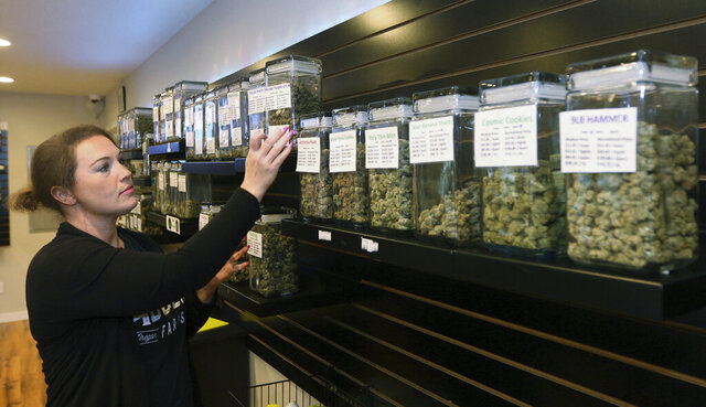 FILE - In this Oct. 26, 2018, file photo, Diana Calvert, River City Retail Marijuana Dispensary manager stocks the shelves with product in Merlin, Ore. Marijuana sales in Oregon along the Idaho state line are 420% the statewide average, according to a state report. Idaho residents are purchasing recreational marijuana in Oregon because it is illegal in Idaho, the report released Friday, Jan. 17, 2020, by the Oregon Office of Economic Analysis said. (Timothy Bullard/The Daily Courier via AP)