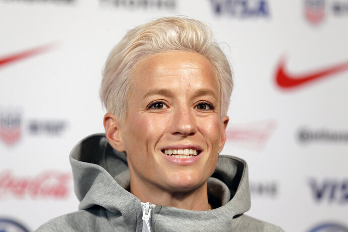 FILE - In this May 24, 2019, file photo, Megan Rapinoe, a member of the United States women's national soccer team, speaks to reporters during a news conference in New York. Seahawks quarterback Russell Wilson, soccer star Megan Rapinoe and three-time WNBA champion Sue Bird will preside over The ESPYS two-hour broadcast airing June 21 on ESPN. All three live in the Seattle area. Rapinoe and Bird are partners who share a household, which conveniently eases some logistics. Wilson's singer-wife, Ciara, is likely to make an appearance, too.  (AP Photo/Seth Wenig, File)