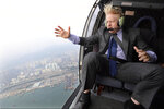 FILE - In this Thursday Oct. 17, 2013 file photo Mayor of London Boris Johnson looks at the skyline during helicopter ride over Hong Kong. (AP Photo/Andrew Parsons/Pool, File)