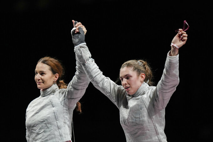 Sofia Pozdniakova, right, celebrates with Sofya Velikaya of the Russian Olympic Committee after winning the gold at the women's individual Sabre final competition at the 2020 Summer Olympics, Monday, July 26, 2021, in Chiba, Japan. (AP Photo/Andrew Medichini)