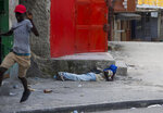 A demonstrator lays down on the ground for cover as another runs away at the sound of gunfire, during a protest to demand the resignation of Haiti's president Jovenel Moise on the 216th anniversary of Battle of Vertieres in Port-au-Prince, Haiti, Monday, Nov. 18, 2019. At least four people were shot and wounded during a small protest in Haiti's capital after a speech by embattled President Moise. A local journalist, a police officer and two protesters were rushed away with apparent bullet wounds. (AP Photo/Dieu Nalio Chery)