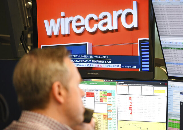 A stockbroker sits in front of a screen with news about the payment service provider Wirecard at the Frankfurt Stock Exchange in Frankfurt, Germany, Monday, June 22, 2020. Germany payment service provider Wirecard AG says it has concluded that two accounts that were supposed to contain 1.9 billion euros (2.1 billion dollars) probably don't exist. (Arne Dedert/dpa via AP)