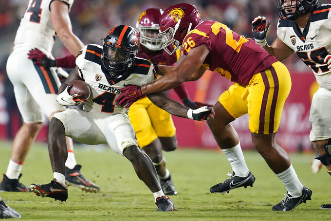 Oregon State running back B.J. Baylor (4) runs next to Southern California linebacker Kana'i Mauga (26) during the first half of an NCAA college football game Saturday, Sept. 25, 2021, in Los Angeles. (AP Photo/Marcio Jose Sanchez)