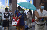 People wear face masks to protect against the spread of the coronavirus and walk in the light rain from approaching Typhoon In-Fa in Taipei, Taiwan, Thursday, July 22, 2021. (AP Photo/Chiang Ying-ying)