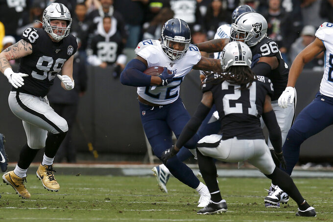 Tennessee Titans running back Derrick Henry (22) runs against Oakland Raiders free safety D.J. Swearinger (21) and defensive end Clelin Ferrell (96) during the first half of an NFL football game in Oakland, Calif., Sunday, Dec. 8, 2019. (AP Photo/D. Ross Cameron)