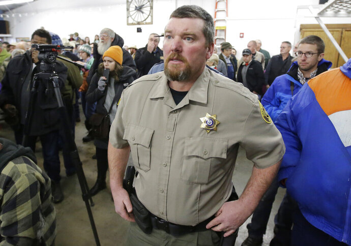 FILE - In this Jan. 6, 2016, file photo, Harney County Sheriff David Ward arrives at a community meeting at the Harney County fairgrounds in Burns, Ore. Ward says he will resign at the end of 2019 because his department is underfunded and he's concerned about liability from unlawful jail conditions. (AP Photo/Rick Bowmer, File)