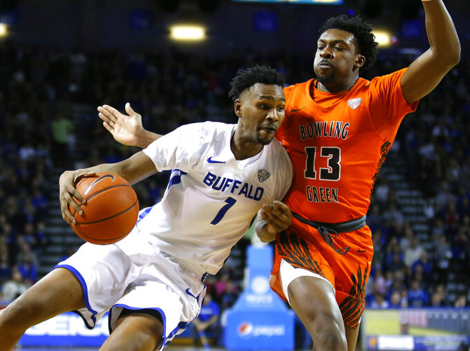 Buffalo forward Montell McRae (1) drives against Bowling Green forward Jeffrey Uju (13) during the first half of an NCAA college basketball game, Friday, March 8, 2019, in Buffalo, N.Y. (AP Photo/Jeffrey T. Barnes)