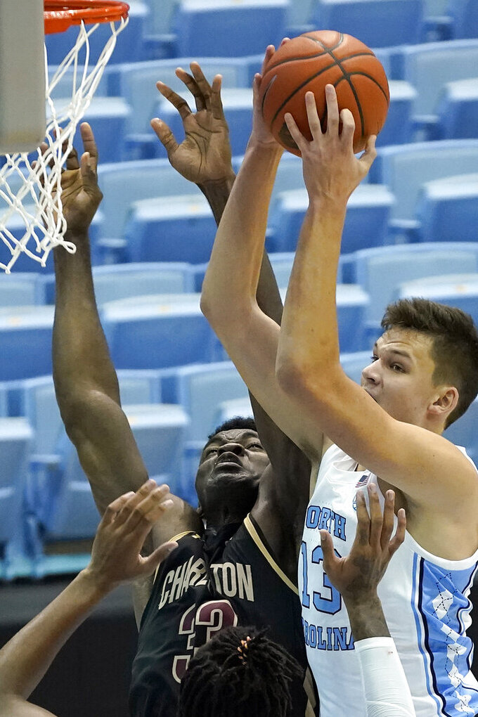 North Carolina forward Walker Kessler (13) grabs a rebound over College of Charleston center Osinachi Smart (33) during the second half of an NCAA college basketball game in Chapel Hill, N.C., Wednesday, Nov. 25, 2020. (AP Photo/Gerry Broome)
