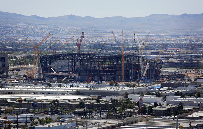 FILE - In this June 4, 2019, file photo, construction cranes surround the football stadium under construction in Las Vegas. Officials in Las Vegas have boosted the cost of a 65,000-seat stadium being built for the NFL's relocated Raiders and UNLV football to $1.9 billion. The Las Vegas Review-Journal reports the Las Vegas Stadium Authority board on Thursday, July 18, 2019, approved $40 million in additions. They include 20 more suites and a field-level club area to be paid for by personal seat license and club seat sales not part of the original budget. (AP Photo/John Locher, File)