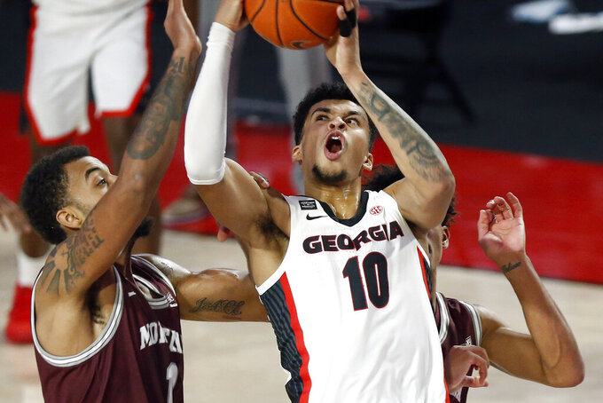 Georgia's Toumani Camara (10) takes a shot while being defended by Montana forward Michael Steadman (1) and Montana forward Michael Steadman (1) during an NCAA college basketball game Tuesday, Dec. 8, 2020, in Athens, Ga. (Joshua L. Jones/Athens Banner-Herald via AP)