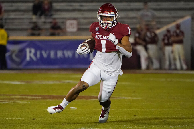 FILE - In this Saturday, Nov. 7, 2020, file photo, Oklahoma running back Seth McGowan (1) carries during an NCAA college football game against Kansas in Norman, Okla. Oklahoma coach Lincoln Riley said receiver Trejan Bridges and running back Seth McGowan are no longer with the program. (AP Photo/Sue Ogrocki, File)