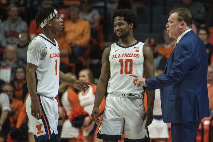 Illinois head coach Brad Underwood, right, talks with Trent Frazier (1) and Andres Feliz (10) during a timeout in the first half of an NCAA college basketball game against Nebraska, Monday, Feb. 24, 2020, in Champaign, Ill. (AP Photo/Holly Hart)