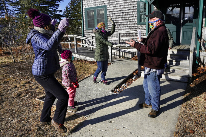 Island residents, Lindsay Eysnogle, left, her daughter, Marina Pickering and Kaitlyn Miller, center, do a happy dance with Mitchell McCormick to celebrate their COVID-19 vaccinations, Friday, March 19, 2021, on Islesford, Maine. Getting the vaccine to the world's farthest corners means delivering it by boat to Maine's islands, traveling by snowmobile to villages in Alaska and navigating complex waterways in Brazil's Amazon. (AP Photo/Robert F. Bukaty)