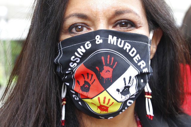 Jeannie Hovland, the deputy assistant secretary for Native American Affairs for the U.S. Department of Health and Human Services, poses with a Missing and Murdered Indigenous Women mask, Wednesday, Aug. 26, 2020, in Anchorage, Alaska. She attended the opening of a Lady Justice Task Force cold case office in Anchorage, which will investigate missing and murdered Indigenous women. (AP Photo/Mark Thiessen)