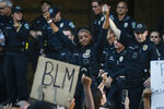 Police officer Alexandra Parker holds her hand up with a fellow officer in front of protesters at the Austin Police Department HQ during a Black Lives Matter rally in Austin, June 4, 2020. George Floyd, a black man, died after being restrained by Minneapolis police officers on May 25 and his death sparked protests. (Lola Gomez/Austin American-Statesman via AP)