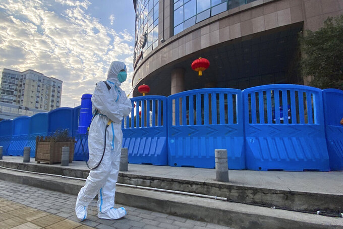 FILE - In this file photo dated Saturday, Feb. 6, 2021, a worker in protectively overalls and carrying disinfecting equipment walks outside the Wuhan Central Hospital where Li Wenliang, the whistleblower doctor who sounded the alarm and was reprimanded by local police for it in the early days of Wuhan's pandemic, worked in Wuhan in central China. A lengthy written report published Thursday March 25, 2021, from a team of international and Chinese scientists on a joint mission to Wuhan aims to help unearth the origins of the coronavirus since it was first detected in China more than a year ago. (AP Photo/Ng Han Guan, FILE)