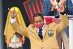 Troy Polamalu, a member of the Pro Football Hall of Fame Centennial Class, gestures after receiving his gold jacket during the induction ceremony at the Pro Football Hall of Fame, Saturday, Aug. 7, 2021, in Canton, Ohio. (AP Photo/David Richard)
