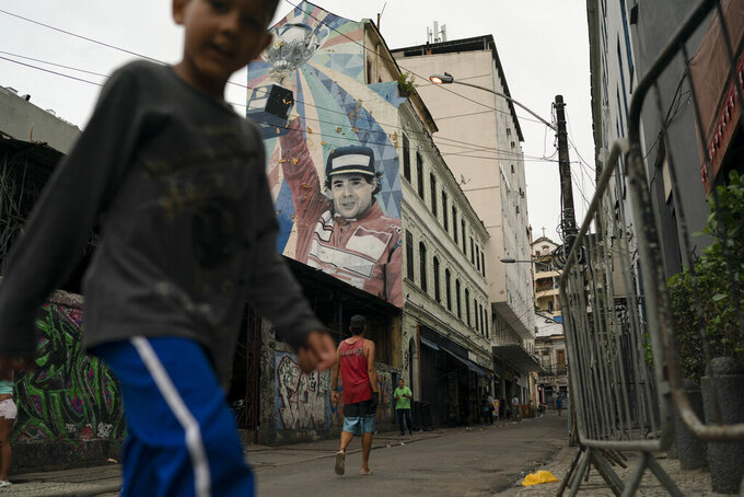 In this Nov. 7, 2019 photo, people walk past a building decorated with mural art depicting legendary Brazilian F1 driver Ayrton Senna, in Rio de Janeiro, Brazil. Rio has the exuberance of samba and Carnival, plus dramatic postcard views of beaches and verdant mountains. Now, to Sao Paulo's chagrin, Rio is pushing for an F1 racetrack, too. (AP Photo/Leo Correa)