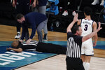 Referee Bert Smith collapses on the court during the first half of an Elite 8 game between Gonzaga and Southern California in the NCAA men's college basketball tournament at Lucas Oil Stadium, Tuesday, March 30, 2021, in Indianapolis. (AP Photo/Michael Conroy)