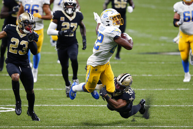 Los Angeles Chargers running back Justin Jackson (22) carries against New Orleans Saints free safety Marcus Williams (43) in the first half of an NFL football game in New Orleans, Monday, Oct. 12, 2020. (AP Photo/Butch Dill)