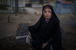 Basima Hidari, 20, sits on the grave of her brother Ali Hidari in Kabul, Afghanistan, Thursday, Sept. 16, 2021. Hidari was injured and her 19-years-old brother Ali Hidari was killed last month when they were trying to enter the airport during the U.S.-led evacuation. (AP Photo/Felipe Dana)
