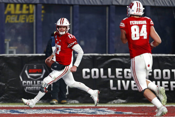 Wisconsin quarterback Jack Coan celebrates his touchdown with tight end Jake Ferguson (84) during the second half against Miami in the Pinstripe Bowl NCAA college football game Thursday, Dec. 27, 2018, in New York. Wisconsin defeated Miami 35-3. (AP Photo/Adam Hunger)