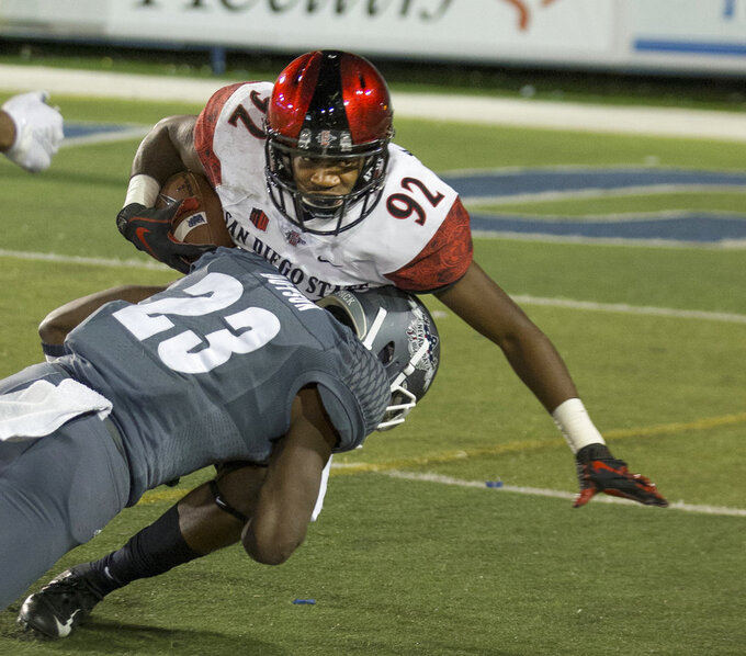 San Diego State's Kobe Smith (92) is hit by Nevada's Jomon Dotson (23) in the second half of an NCAA college football game in Reno, Nev., Saturday, Oct. 27, 2018. (AP Photo/Tom R. Smedes)