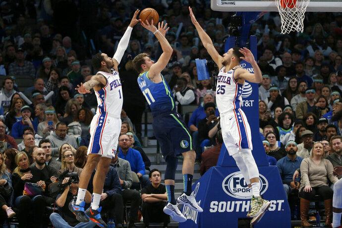 Philadelphia 76ers forward Mike Scott (1) blocks a shot by Dallas Mavericks forward Luka Doncic (77) as 76ers guard Ben Simmons (25) defends during the first half of an NBA basketball game in Dallas, Saturday, Jan 11, 2020. (AP Photo/Michael Ainsworth)