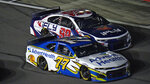 Jamie McMurray (77) beats Daniel Suarez (99) off pit road during the first NASCAR Daytona 500 duel qualifying auto race Thursday, Feb. 11, 2021, at Daytona International Speedway in Daytona Beach, Fla. (AP Photo/Chris O'Meara)