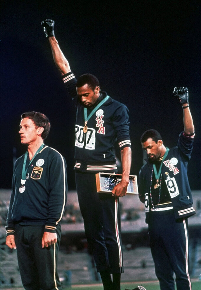 FILE - In this Oct. 16, 1968, file photo, extending gloved hands skyward in protest, U.S. athletes Tommie Smith, center, and John Carlos stare downward during the national anthem after Smith received the gold and Carlos the bronze in the men's 200 meters at the Summer Olympics in Mexico City. Australian silver medalist Peter Norman is at left. In a major shift in policy, the U.S. Olympic and Paralympic Committee committed to not sanction athletes who use their platform for social demonstrations. The USOPC stance sets up the possibility for conflict and confusion at the Tokyo Games, where the IOC will be in charge. (AP Photo/File)