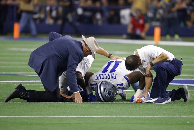 Dallas Cowboys linebacker Micah Parsons (11) is attended to by team staff on the field in the second half of an NFL football game against the Philadelphia Eagles in Arlington, Texas, Monday, Sept. 27, 2021. (AP Photo/Ron Jenkins)