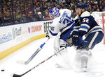 Tampa Bay Lightning goalie Curtis McElhinney, left, tries to clear the puck in front of Columbus Blue Jackets forward Emil Bemstrom, of Sweden, during the second period of an NHL hockey game in Columbus, Ohio, Monday, Feb. 10, 2020. (AP Photo/Paul Vernon)