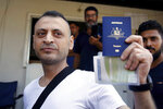 Australian-Lebanese dual citizen Amer Khayyat shows his Australian passport to journalists, after his release from prison in Roumieh, east of Beirut, Lebanon, Friday, Sept. 20, 2019. Lebanese authorities have released the Lebanese-Australian who had been detained in Lebanon for more than two years after he was found innocent in an alleged plot to bring down a passenger plane bound for the United Arab Emirates from Sydney. (AP Photo/Bilal Hussein)