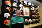 Steve Spurrier stands in front of a display of helmets of teams that he previously played for or coached at his new restaurant, the Gridiron Grill, Thursday, June 17, 2021, in Gainesville, Fla. The restaurant doubles as Spurrier's personal museum. (AP Photo/John Raoux)