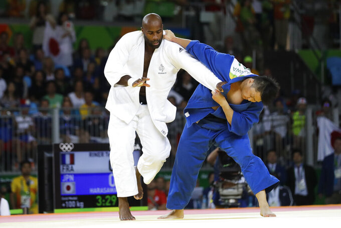 FILE - In this Friday, Aug. 12, 2016 file photo, France's Teddy Riner, left, competes against Japan's Hisayoshi Harasawa for the gold medal during the men's over 100-kg judo competition at the 2016 Summer Olympics in Rio de Janeiro, Brazil. Judo is coming home at the Tokyo Olympics, and the Japanese team is under a world of pressure. All of Japan's stars will be tested, and not all are gold medal favorites. The rest of the world has dynamic champions, and the biggest is 6-foot-8 French heavyweight Teddy Riner, who won two Olympic gold medals and went undefeated in 154 consecutive matches for a full decade from 2010 to 2020 until he lost twice last year. (AP Photo/Markus Schreiber, File)