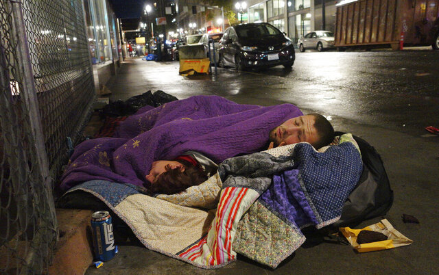 FILE - In this Sept. 18, 2017, file photo, two people sleep on a street in downtown Portland, Ore. Voters in metropolitan Portland will be asked Tuesday, May 19, 2020 to approve taxes on personal income and business profits that would raise $2.5 billion over a decade to fight homelessness even as Oregon grapples with the coronavirus pandemic and its worst recession in decades. (AP Photo/Ted S. Warren, File)