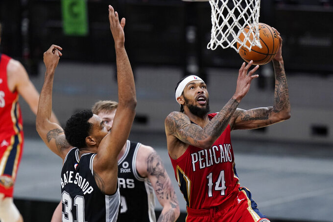 New Orleans Pelicans forward Brandon Ingram (14) scores past San Antonio Spurs forward Keita Bates-Diop (31) during the first half of an NBA basketball game in San Antonio, Saturday, Feb. 27, 2021. (AP Photo/Eric Gay)