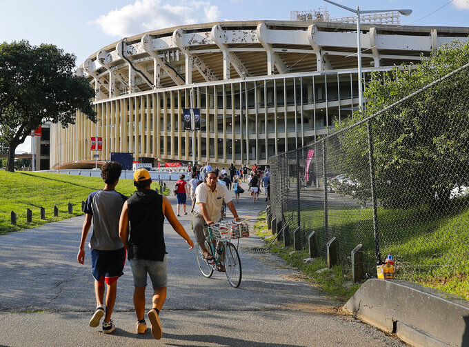 FILE - In this Aug. 5, 2017, file photo people make their way to RFK Stadium in Washington before an MLS soccer match between D.C. United and Toronto FC. The stadium, the former home of the NFL's Washington Redskins, Major League Baseball's Washington Nationals and Senators, and Major League Soccer's D.C. United, will be demolished by 2021, local officials in Washington said. (AP Photo/Pablo Martinez Monsivais, File)