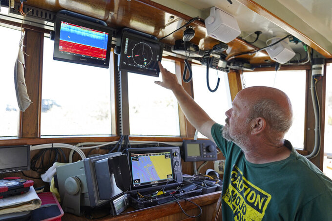 Salmon fisherman Mike Hudson looks over instruments in the cabin of his boat at the Berkeley, Calif., Marina on Thursday, July 22, 2021. Baby salmon are dying by the thousands in one river and an entire run of endangered salmon could be wiped out in another. The plummeting catch has led to skyrocketing retail prices for salmon, hurting customers who say they can no longer afford the $35 per pound of fish, said Hudson, who has spent the last 25 years catching and selling salmon at farmers' markets in Berkeley. (AP Photo/Eric Risberg)