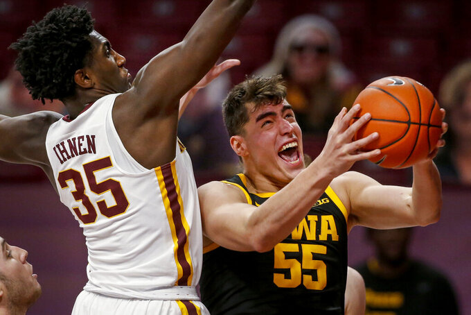 Iowa center Luka Garza (55) works to the basket as Minnesota forward Isaiah Ihnen (35) defends during the second half of an NCAA college basketball game Friday, Dec. 25, 2020, in Minneapolis. Minnesota won 102-95 in overtime. (AP Photo/Bruce Kluckhohn)
